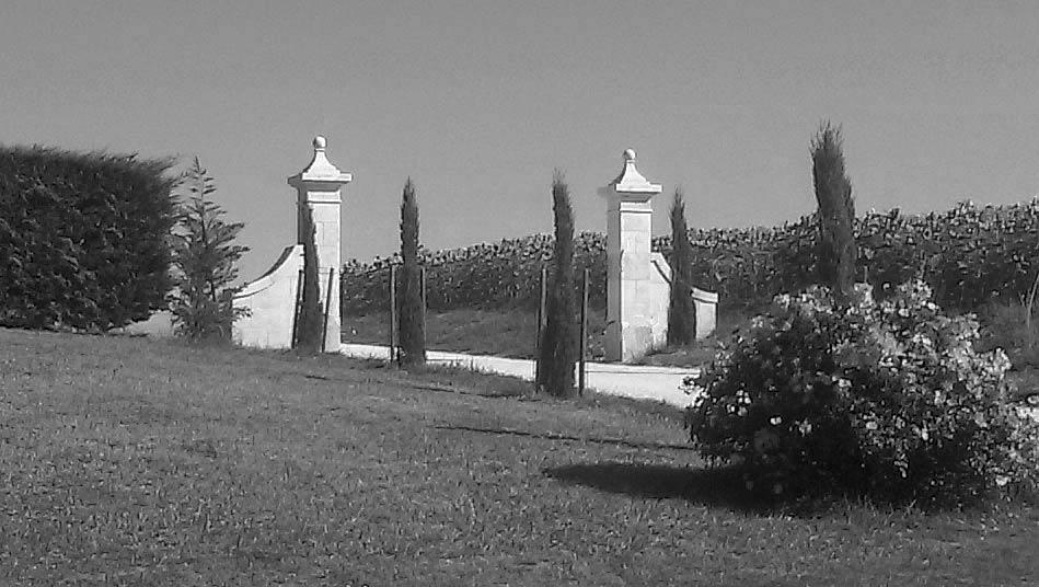 piliers d'entrée avec chapiteau orné d'une boule en pierre taillée dans la masse