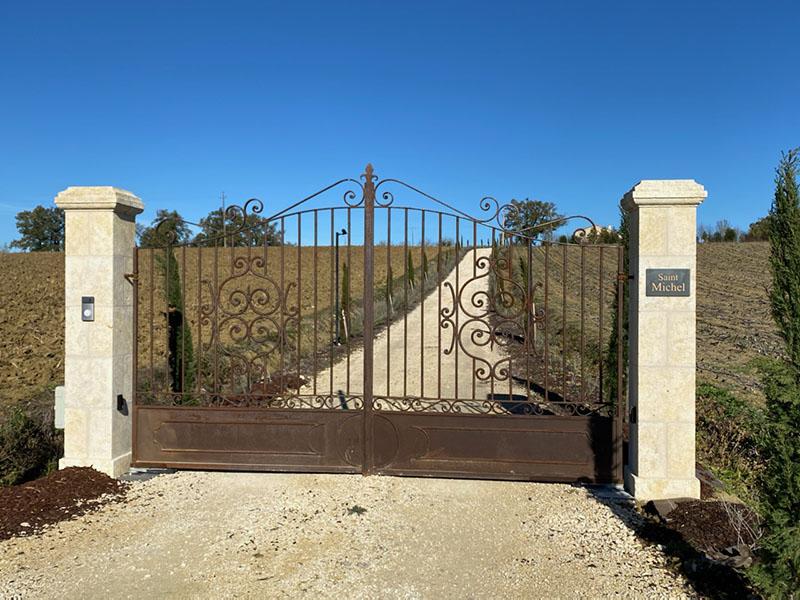 Piliers d'entrée en pierre avec portail en ferronnerie