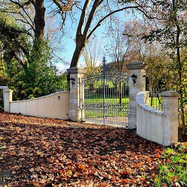 paire de piliers de portail en pierre avec murets et grille en fer forgé